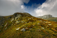 Alpine landscape in a cloudy day. Landscape with rocky mountains and hiking trail Stock Photo