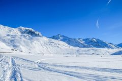 Alpine landscape with blue skies. An Alpine landscape with fresh snow and blue skies above royalty free stock image