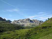 Alpine landscape. With a high peak, a green valley and a blue sky Stock Photography