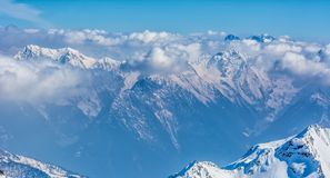 Alpine landscape with peaks covered by snow and clouds Royalty Free Stock Image