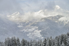 Alpine landscape with snowfall forest and village Royalty Free Stock Image