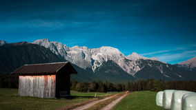 Alpine landscape. View of the Mieminger kette in Tirol, Austria. Perfect composition with barn, bails, mountain, and sky Royalty Free Stock Photo