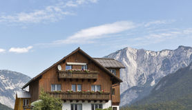 Alpine landscape with wooden house and high mountains Royalty Free Stock Image