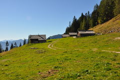 Alpine landscape with wooden huts. Green meadow in austrian alps with some wooden huts stock images