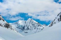 Alpine Landschaft mit den Spitzen umfasst durch Schnee und Wolken Lizenzfreie Stockfotos