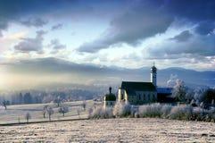 Alpine Landschaft mit Kirche im eisigen Morgen Lizenzfreie Stockbilder