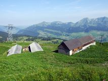 Alpine livestock farms and stables on the slopes of Churfirsten mountain range in the Toggenburg region. Canton of St. Gallen, Switzerland stock images