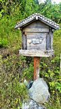Alpine mailbox, weathered gray wood with cow carving. Rustic Alpine mailbox of weathered gray wood, with cow carving, on wooden post in field of green foliage Stock Images