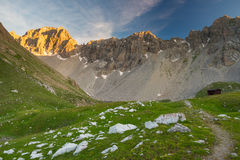Alpine meadow and pasture set amid high altitude mountain range at sunsets. The Italian Alps, famous travel destination in summert Royalty Free Stock Image