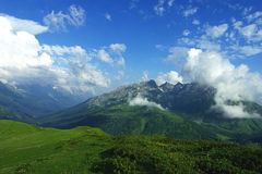 Alpine meadows, mountains and lots of white clouds with beautiful summer landscape Royalty Free Stock Photography