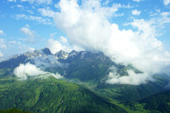 Alpine meadows, mountains and lots of white clouds with beautiful summer landscape. Far away with many mountain peaks on the horizon, the blue sky and clouds Royalty Free Stock Photography