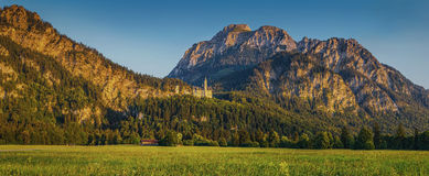 Alpine mountain landscape with famous Neuschwanstein Castle at sunset Stock Image