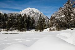 Alpine mountain pass winter scenery landscape by lake lago del predil in sunny blue sky in snowfall, italy Stock Photos