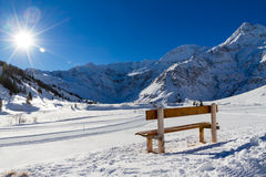 Alpine mountain scenery with bench inviting sunbathing on a mountain Sun Stock Images