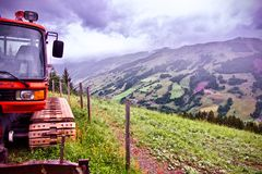 Alpine mountain under a foggy sky with a excavator in the foreground in Saalbach, Austria Stock Images