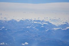 Alpine mountains in blue and white clouds aerial view royalty free stock image