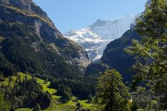 Alpine mountains range as seen from Grindelwald. In Switzerland. There are slopes of rocky mountains, snowy peaks and a glacier can be seen Stock Photos
