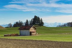 Alpine mountains spring landscape with wooden shed Royalty Free Stock Photo