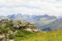 Alpine panorama with slate stone in the foreground, Montafon in Austria. Alpine panorama with slate stone and meadow in the foreground, Montafon in Austria Royalty Free Stock Images