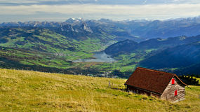 Alpine Pasture Switzerland. A scenic view of an alpine farming hut and pasture overlooking the mountains and lakes of central switzerland Royalty Free Stock Photography