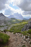 Alpine path. An alpine path in a beautiful valley and scenery,with the tofane mountains on the background Royalty Free Stock Photos