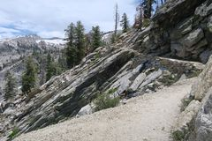Alpine Path. Rocky alpine trail with steep embankment and overview of distant mountains on the trail to Heather Lake, Sequoia National Park, California, United royalty free stock photo