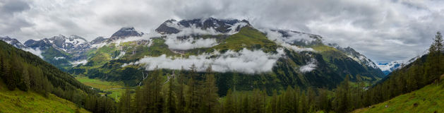 Alpine peaks of the mountains in the clouds - panorama Royalty Free Stock Photography