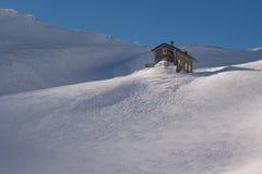 Alpine refuge below mountain ridge in winter on windswept snow stock photography