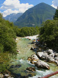 Alpine river landscape. Beautiful landscape of alpine river Soca in Slovenia, Europe Fast-flowing alpine stream, group of kayakers taking a break on the beach stock image