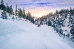 Alpine road mapped out in snow, Austria. Winter scenery with the Austrian Alps mountains and its forests and roads, covered by snow, while a snow grooming Royalty Free Stock Image