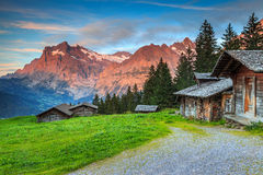 Alpine rural landscape with old wooden chalets,Grindelwald,Switzerland,Europe. Beautiful alpine landscape,old Swiss traditional wooden hut and magical sunset Stock Photo