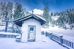 Alpine rustikale Kapelle im Winterdekor Stockfotografie