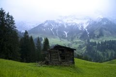 Alpine scenery with barn shed and snow mountain ba Stock Photography