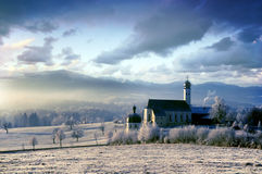 Alpine scenery with church in the frosty morning. Beautiful frosty morning in the alpine scenery with pictursque church royalty free stock images
