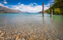 Alpine scenery from Dart River bed in Kinloch, New Zealand. Mountain and wooden piers at Kinloch, low angle view from the Dart river bed. Dart River is flowing Royalty Free Stock Image