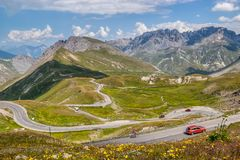 Alpine serpentine road to the Col du Galibier pass. Alpine Serpentine Road in high mountains - Steep road with cyclists and cars between the village Valloire royalty free stock image