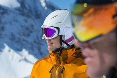 Alpine ski couple - race face. Sport female face with helmet - beauty in winterlandscape Stock Photo