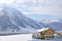 Winter Sport hut covered in snow. Alpine ski hut covered in snow with mountain range in background and slope nearby Stock Photos