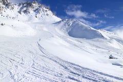 Alpine ski piste in snowy mountain winter sports resort Stock Photos