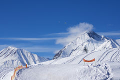 Alpine ski resort of snow-covered rocks bright winter day. Royalty Free Stock Photo