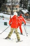 Alpine ski school. Instructor and student in colorful ski equipment stock image