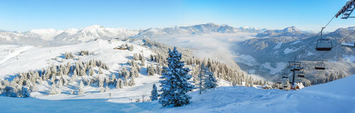 Alpine ski slope mountain winter panorama with ski lift. Skiers and snow covered forest royalty free stock images
