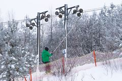 Alpine skier climbs up the hill on a ski lift in winter. Snow-covered pine forest. Mechanization of a ski resort for a winter stock image