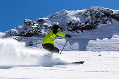Alpine skier on piste, skiing downhill Royalty Free Stock Photo