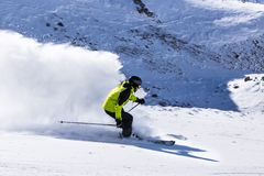 Alpine skier on piste, skiing downhill Stock Image