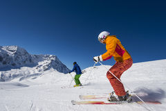 Alpine skiing in the alp mountains. Two downhill skiiers in action Stock Photos