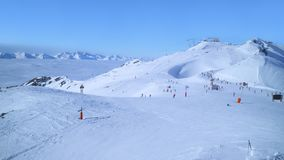 Alpine skiing slopes above cloudy valleys Stock Images