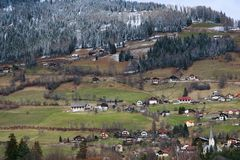 Alpine spring fields and traditional wooden houses stock images