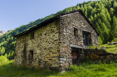 Alpine stone shepherd's hut in a peasant village in the background of the Alps Royalty Free Stock Photography