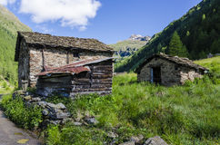 Alpine stone shepherd's hut in a peasant village in the background of the Alps Stock Photography